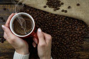Kvinne som holder en kaffekopp. I bakgrunnen: kaffebønner